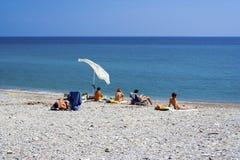 Leute, die auf dem Strand in Albenga ein Sonnenbad nehmen Stockbilder