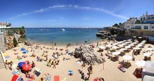 Leute, die auf dem Strand in Cascais, Portugal ein Sonnenbad nehmen Lizenzfreie Stockbilder