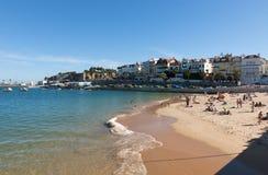 Leute, die auf dem Strand in Cascais, Portugal ein Sonnenbad nehmen Lizenzfreies Stockfoto