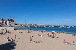 Leute, die auf dem Strand in Cascais, Portugal ein Sonnenbad nehmen Lizenzfreie Stockfotografie