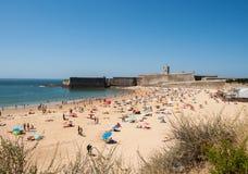 Leute, die auf dem Strand in Cascais, Portugal ein Sonnenbad nehmen Stockfotos