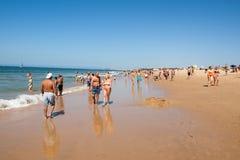 Leute, die auf dem Strand in Cascais, Portugal ein Sonnenbad nehmen Stockfotografie