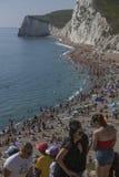 Leute, die auf dem Strand - Durdle-Tür, England ein Sonnenbad nehmen Stockfotografie