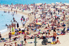 Leute, die auf dem Strand ein Sonnenbad nehmen Stockbilder