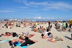 Leute, die auf dem Strand stillstehen Lizenzfreie Stockfotos