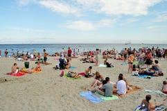 Leute, die auf dem Strand stillstehen Stockfotografie