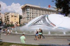 Leute, die auf den Hintergrund der UEFA-Kugel schlendern Stockbilder