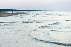Leute, die auf den sandigen Strand im Sonnenuntergang gehen Stockfoto