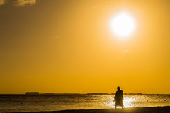 Leute, die auf den Strand bei Sonnenuntergang gehen Stockbilder
