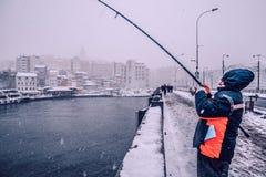 Leute, die auf der galata Brücke an einem schneebedeckten Tag im Winter fischen Stockfotos