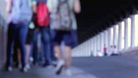 Leute, die auf eine überdachte Brücke gehen. Undeutlich, unscharf. stock video
