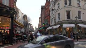 Leute, die auf eine verkehrsreiche Straße in Dublin gehen stock footage