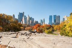 Leute, die auf einem Felsen im Central Park sitzen Stockfotografie