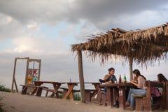 Leute, die auf einem Strandrestaurant essen Stockfotografie