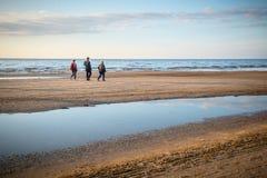 Leute, die auf einen Strand nahe Meer gehen lizenzfreie stockfotografie