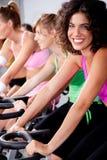 Leute, die auf Fahrräder in einer Gymnastik spinnen stockbild