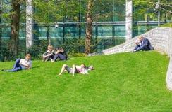 Leute, die auf Gras im Jubiläum-Park, Canary Wharf sitzen und liegen Stockfotos