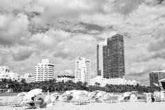 Leute, die auf Klappstühlen unter grauen Regenschirmen auf Strand sich entspannen Lizenzfreie Stockfotografie