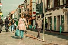 Leute, die auf Oliver Plunkett St, eine der Stadt ` s Hauptstraßen für Speicher, Straßenausführende, Restaurants und beschäftigte Stockbilder