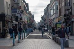 Leute, die auf Oliver Plunkett St, eine der Stadt ` s Hauptstraßen für Speicher, Straßenausführende, Restaurants und beschäftigte Stockfoto