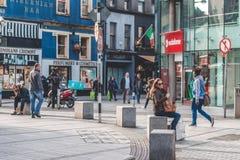 Leute, die auf Oliver Plunkett St, eine der Stadt ` s Hauptstraßen für Speicher, Straßenausführende, Restaurants und beschäftigte Stockfotos