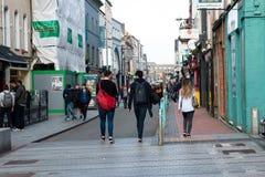 Leute, die auf Oliver Plunkett St, eine der Stadt ` s Hauptstraßen für Speicher, Straßenausführende, Restaurants und beschäftigte Stockbild
