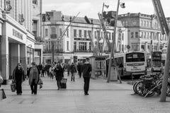 Leute, die auf Patrick Street im Korken, in der Stadt ` s Hauptstraße für Speicher, in den Straßenausführenden, in den Restaurant Stockfotografie