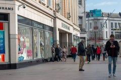 Leute, die auf Patrick Street im Korken, in der Stadt ` s Hauptstraße für Speicher, in den Straßenausführenden, in den Restaurant Lizenzfreie Stockfotografie