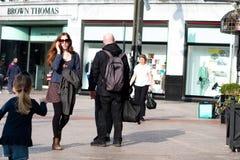 Leute, die auf Patrick Street im Korken, in der Stadt ` s Hauptstraße für Speicher, in den Straßenausführenden, in den Restaurant Stockbilder