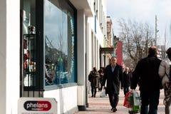 Leute, die auf Patrick Street im Korken, in der Stadt ` s Hauptstraße für Speicher, in den Straßenausführenden, in den Restaurant Stockfotos