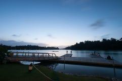 Leute, die auf Plattform durch See am Abend sich entspannen Lizenzfreie Stockfotografie