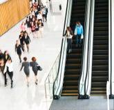Leute, die auf Rolltreppe hetzen stockfoto