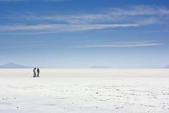 Leute, die auf Salz von Salar de Uyuni gehen stockbild