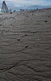 Leute, die auf sandigem Strand mit Bergen im Hintergrund fischen Lizenzfreie Stockfotos