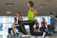 Leute, die auf Schritt in der Aerobic-Klasse trainieren Stockbilder