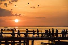 Leute, die auf Sonnenuntergang über Brücke auf See gehen Stockbild