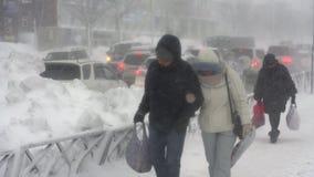 Leute, die auf Stadt während der schweren Schneefälle, pazifischer Schneewirbelsturm gehen stock footage