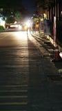 Leute, die auf Straße an Nachtwerfendem Schatten gehen Stockfotografie