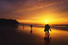 Leute, die auf Strand bei Sonnenuntergang gehen Lizenzfreie Stockfotos