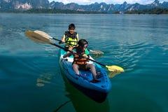 Leute, die auf szenischem See im Sommer, THAILAND canoeing sind Stockbild