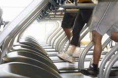 Leute, die auf Tretmühlen im Fitnessstudio laufen Stockbilder