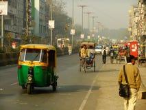 Leute, die auf verkehrsreiche Straße von Delhi, Indien gehen Lizenzfreie Stockbilder