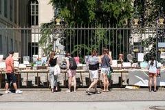 Leute, die aus zweiter Hand Bücher nach Verkauf auf Flohmarkt vor der Humboldt-Universität in Berlin suchen stockbilder