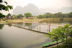 Leute, die Bambusbrücke auf Kalksteingebirgshintergrund führen Stockbilder