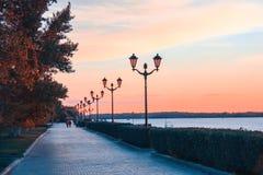 Leute, die bei dem Sonnenuntergang im Stadtdamm gehen stockbilder