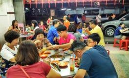 Leute, die berühmtes Lebensmittel von Melaka - Satay Celup essen stockbilder
