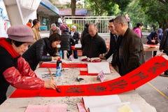 Leute, die chinesische Rollen des neuen Jahres schreiben lizenzfreies stockfoto