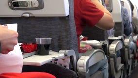 Leute, die das Fluglinienlebensmittel während eines Fluges essen