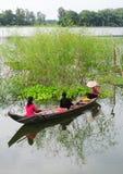 Leute, die das hölzerne Boot auf See in Phuyen, Vietnam rudern lizenzfreie stockbilder