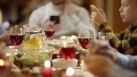 Leute, die das Internet auf Smartphones durch Christmsa-Tabelle, Abschluss oben auf jeder surfen stock footage